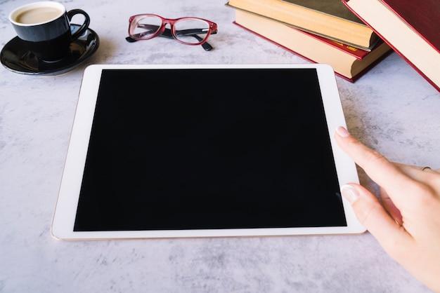 Mano tocando tablet sobre un escritorio