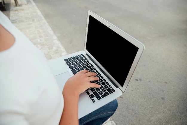 Mano tocando el teclado del ordenador portátil con maqueta