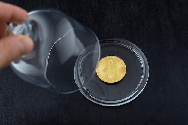 La mano toma el frasco de vidrio debajo del cual hay bitcoin. concepto de inestabilidad de criptomonedas.