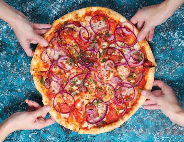 La mano toma un trozo de pizza casera sobre hormigón azul. vista superior