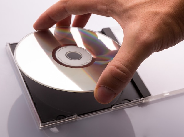 Mano tomando el disco dvd de la caja.