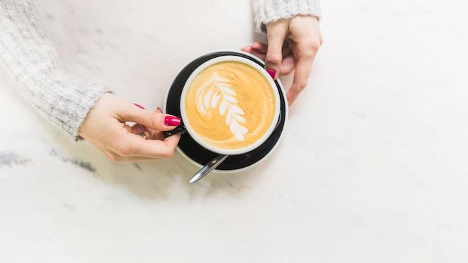 Mano tomando la taza con café