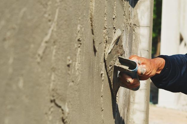 Mano del trabajador de enlucido de cemento en la pared