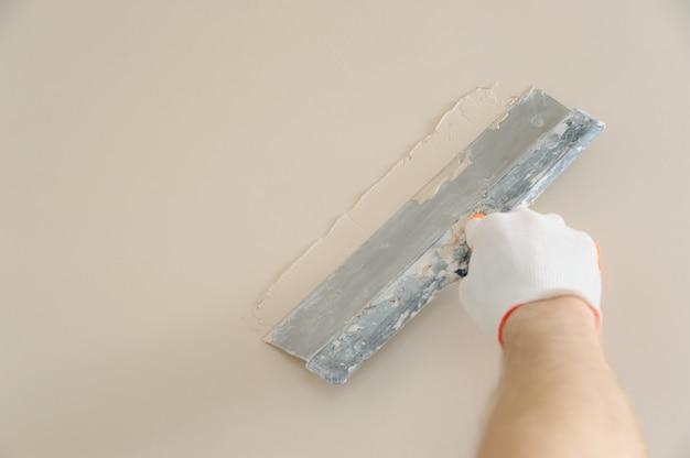La mano del trabajador enyesando una pared con una espátula larga