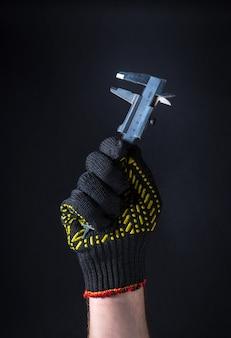 La mano del trabajador en el guante sostiene la pinza sobre un fondo oscuro. idea para construir o renovar