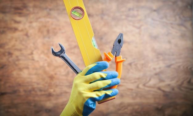 Mano de trabajador sosteniendo el nivel, llave, alicates. herramientas de trabajo