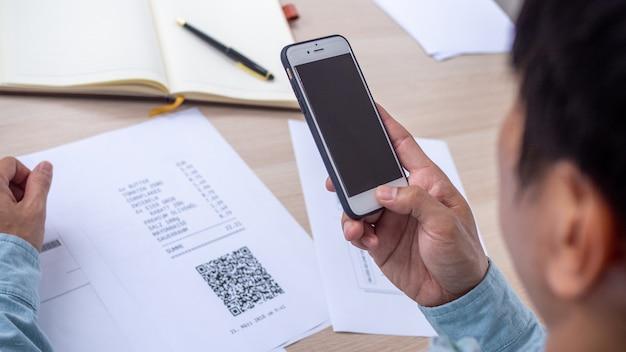 La mano usa el teléfono para escanear el código qr para recibir un descuento al pagar facturas de electricidad en la oficina.