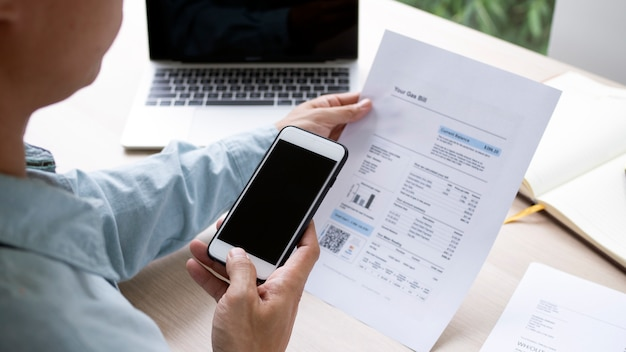 La mano usa el teléfono para escanear el código qr para recibir un descuento al pagar facturas de electricidad en la oficina