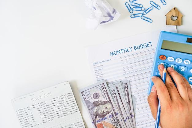 Mano usando la calculadora que calcula el presupuesto mensual con la libreta y nosotros el plano del billete de banco en el fondo blanco.