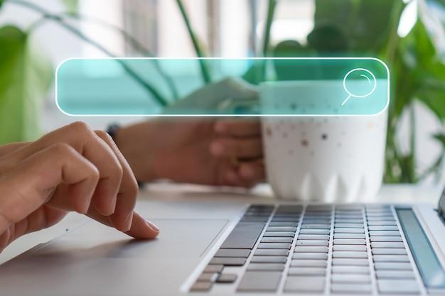 Mano usando una computadora portátil o computadora buscando información en internet con el icono del cuadro de búsqueda y copyspace.