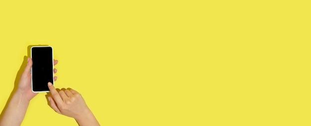 Mano usando gadgets, dispositivo en vista superior, pantalla en blanco con copyspace, estilo minimalista. tecnologías, modernas, marketing. espacio negativo para anuncio, volante. color amarillo en la pared. elegante, de moda.