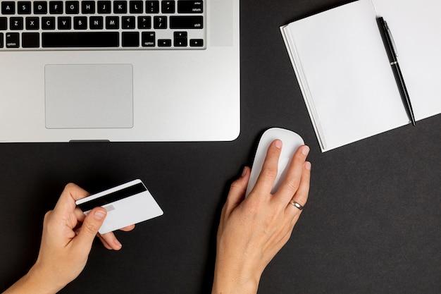 Mano usando el mouse y sosteniendo una tarjeta de crédito