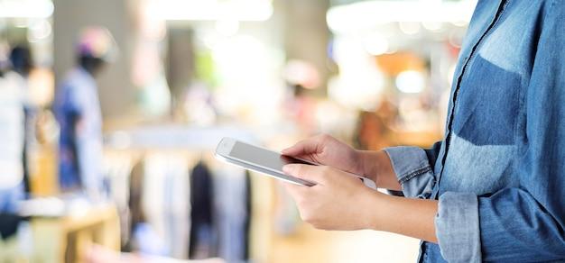 Mano usando tableta sobre tienda de desenfoque con fondo de luz bokeh
