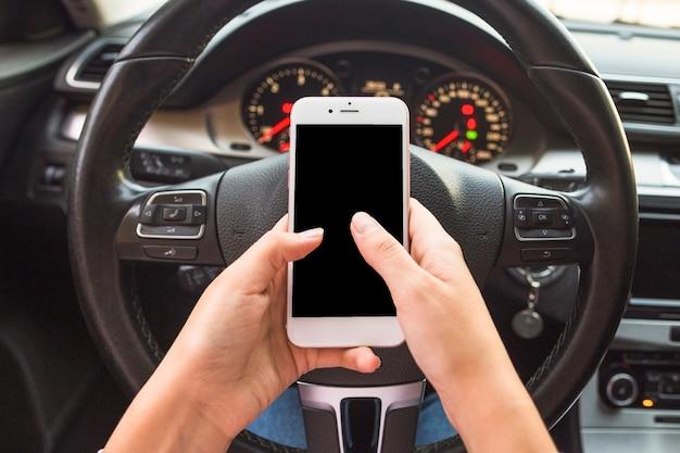 Mano usando teléfono celular en frente del volante en el coche