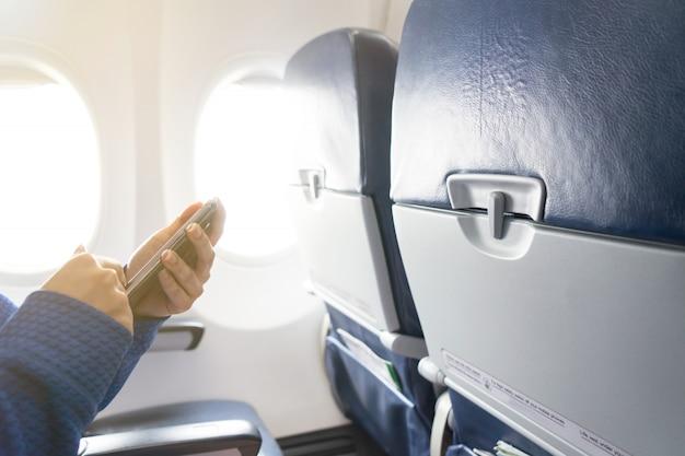 Mano usando teléfono inteligente y ventana en avión con asientos en la cabina