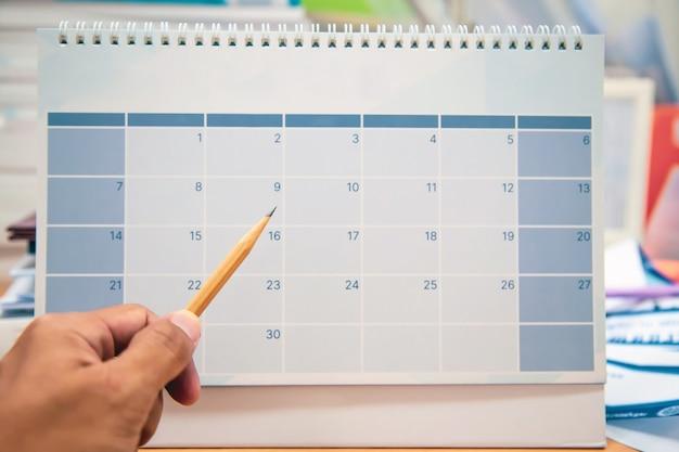 Mano use lápiz tome nota de mensaje de nota en el calendario.