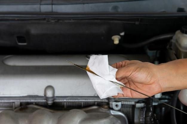 Mano de una varilla de nivel de aceite mecánico del coche