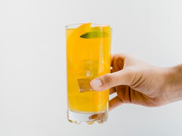 Mano con vaso de jugo de naranja frío