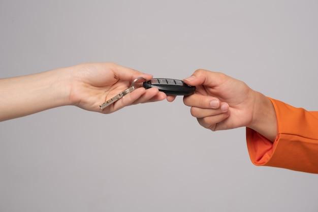 La mano de la vendedora envía las llaves del automóvil al cliente sobre fondo gris