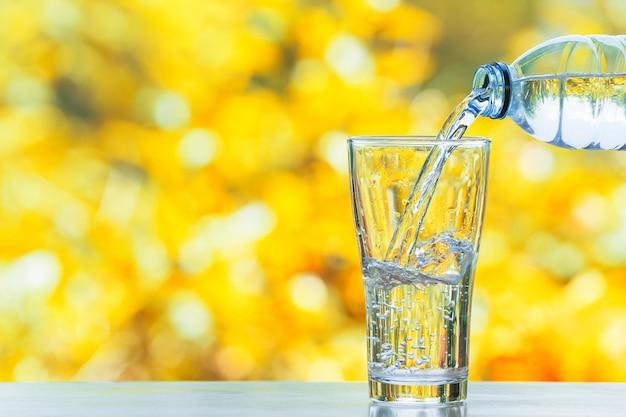 Mano vertiendo agua en botella en vidrio