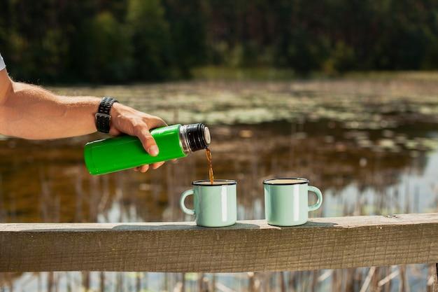 Mano vertiendo bebida en tazas