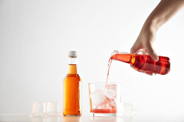 La mano vierte la bebida de sidra de bayas en un vaso con cubitos de hielo cerca de una botella sin etiqueta cerrada sellada con aperol naranja