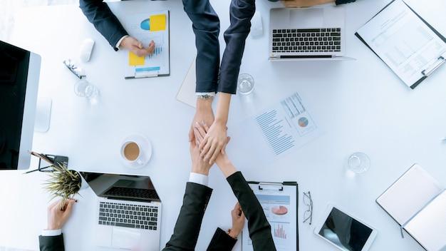 La mano de vista superior del equipo de negocios durante la conferencia de reunión son documentos de trabajo
