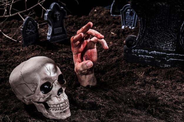 Mano viva con sangre que sobresale de la tumba