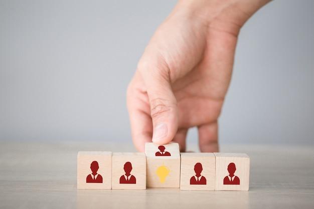 La mano voltea el cubo con la bombilla del icono y el símbolo humano, la idea creativa y el concepto de innovación.
