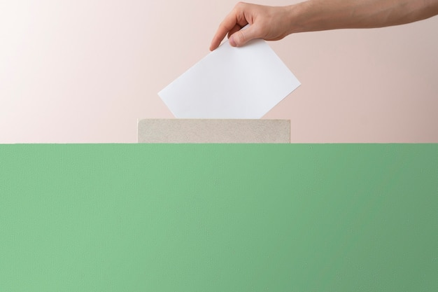 Una mano de votante puso papel en la urna, elección de democracia