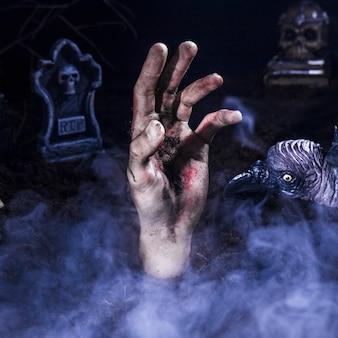 Mano de zombie y cuervo espeluznante en el cementerio de halloween