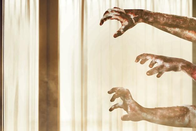 Mano de zombie con sangre y herida en una casa abandonada