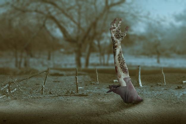 Mano de zombie con sangre y herida levantada del suelo