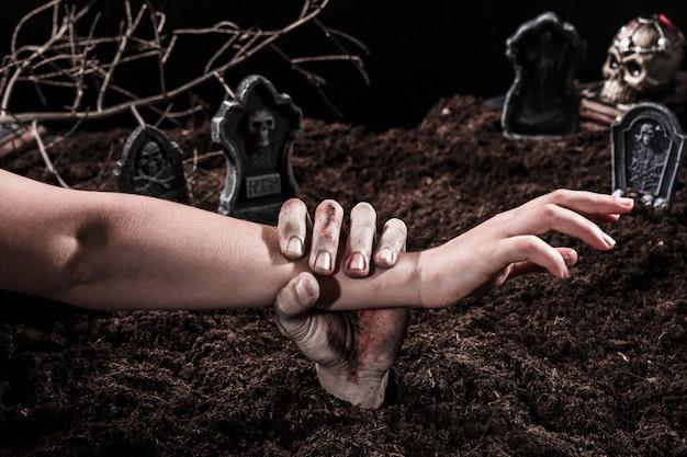 Mano de zombie sosteniendo el brazo de la persona en el cementerio de halloween