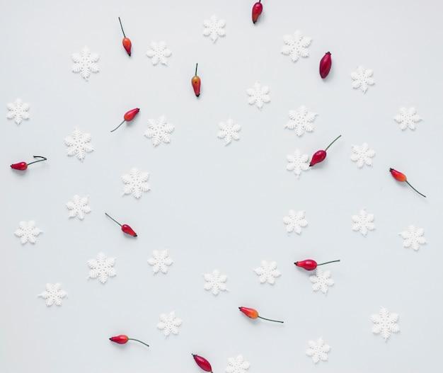 Manojo de bayas rojas y copos de nieve falsos