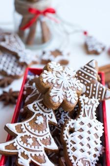 Manojo de pan de jengibre tradicional de navidad con glaseado en una caja de papel rojo