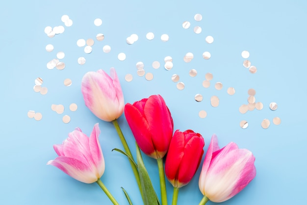 Manojo de diferentes flores frescas brillantes cerca de confeti