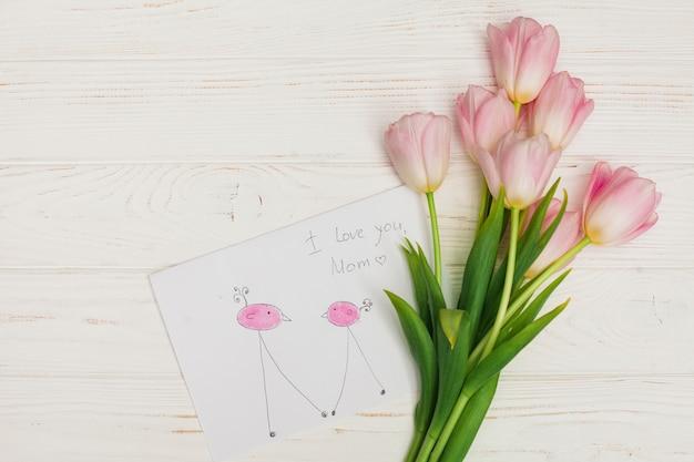Manojo de flores y dibujo infantil en escritorio de madera