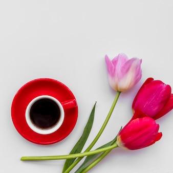 Manojo de flores frescas cerca de la taza de café