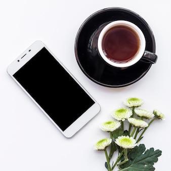 Manojo de flores frescas con taza de café y teléfono inteligente