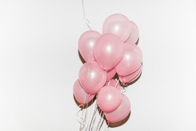 Manojo de globos rosados aislados en el fondo blanco