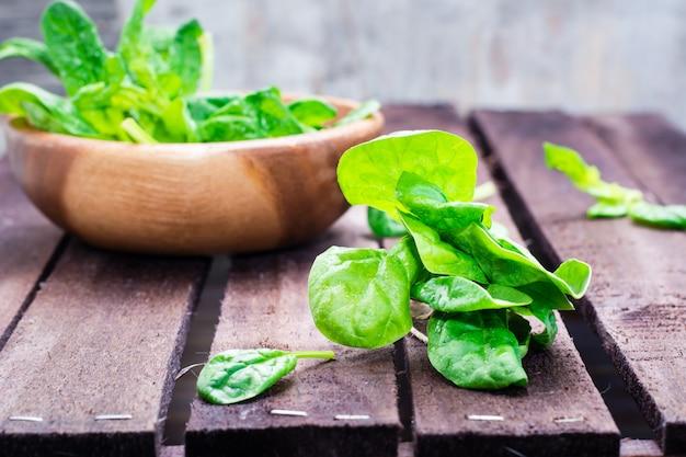 Manojo de hojas frescas de espinacas y hojas de espinacas en un recipiente sobre una mesa de madera