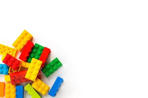 Manojo de ladrillos coloridos del constructor de plastick en blanco. juguetes populares copyspace
