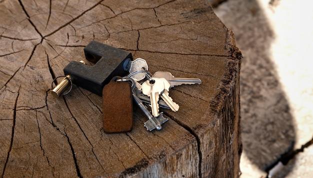 Un manojo de llaves y un candado se encuentran en una madera.