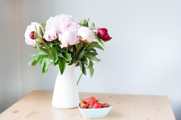 Manojo de peonías rosadas en florero y fresa en la mesa de madera.