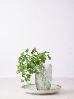 Manojo de perejil fresco con gotas de agua sobre las hojas en un vaso en un plato.