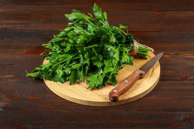 Un manojo de perejil verde en una mesa de madera con un cuchillo