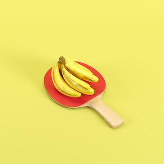 Manojo de plátanos amarillos maduros en la paleta del ping-pong aislada en fondo amarillo