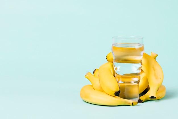 Manojo de plátanos detrás de un vaso de agua.