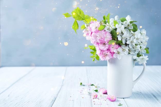 Manojo precioso de las flores salvajes en florero de cerámica en la tabla en fondo de madera
